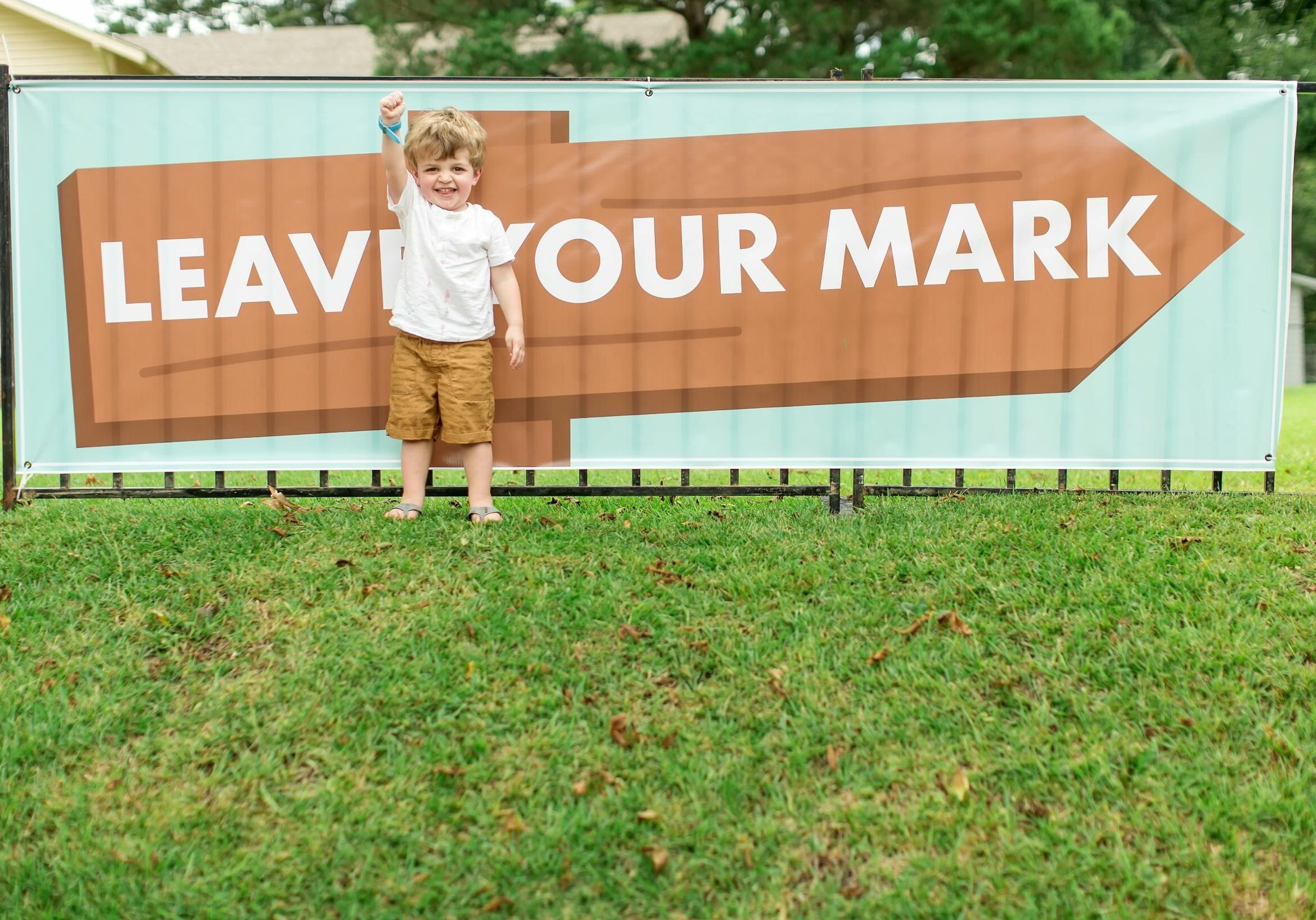 """A little boy raising his fist in front of a sign that reads """"Leave Your Mark"""""""